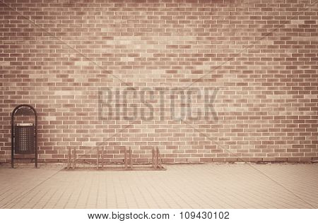 Brick grunge weathered brown wall background with walkway and garbage can