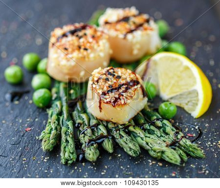 Scallops With Sesame Seeds , Asparagus, Lemon And Green Peas On A Black Plate