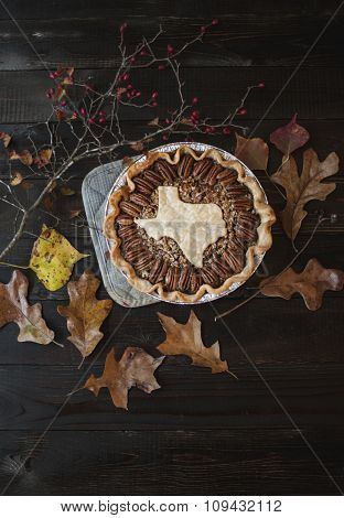 Pecan Pie With Texas Cut-Out On Pie With Fall Leaves and Branches Around It