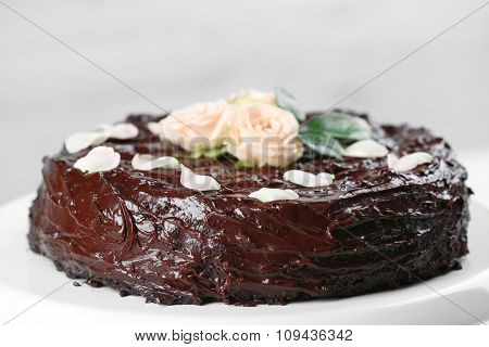Chocolate cake decorated with flowers on white background