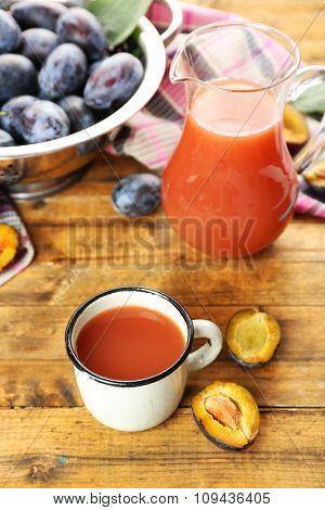 Plum Juice in jar and mug with fresh fruits