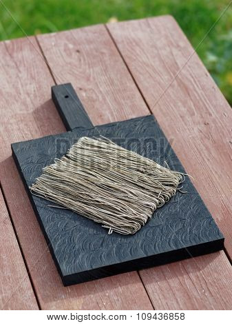 Squid ink pasta on black wooden board