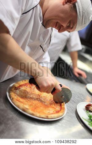 chef baker in white uniform cutting pizza at kitchen