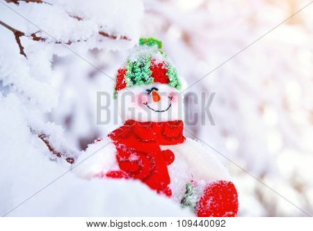 Closeup photo of cute little snowman toy sitting in the snow outdoors, traditional symbol of winter, happy Christmas holidays