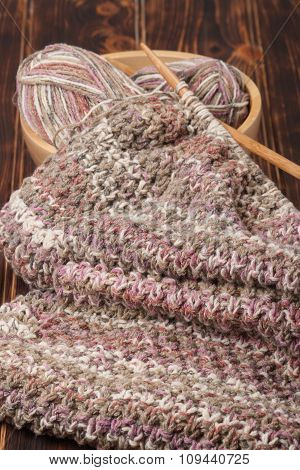 Knitting of Scarf or Snood. Yarn Balls. Wooden Knit Needles
