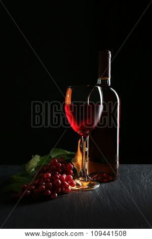 A bottle and a glass of wine, red grapes, on grey-black background