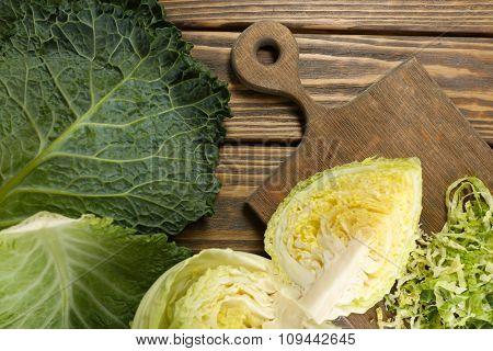 Cut savoy cabbage on wooden cutting board closeup