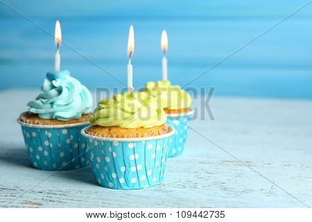 Sweet tasty cupcakes with candles on blue wooden background