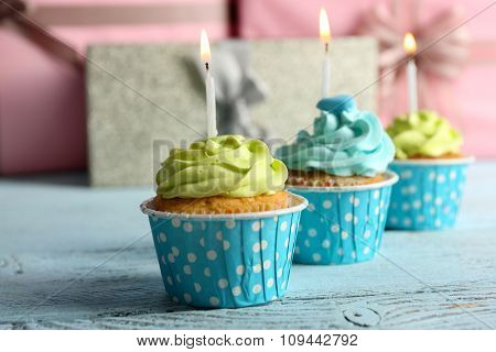 Delicious cupcakes with candles on violet table against wooden background