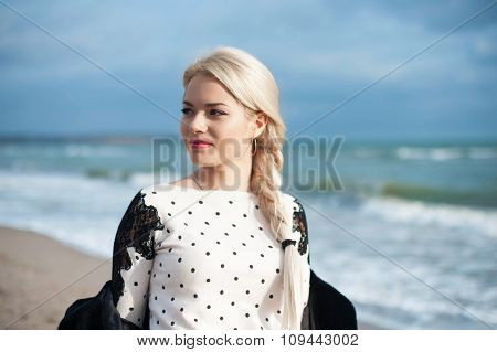 Portrait of the beautiful blonde woman at  sunny autumn day relaxing on coast feeling good