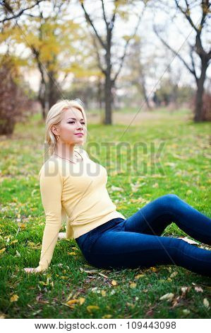 Young beautiful  woman sitting on grass  looking away