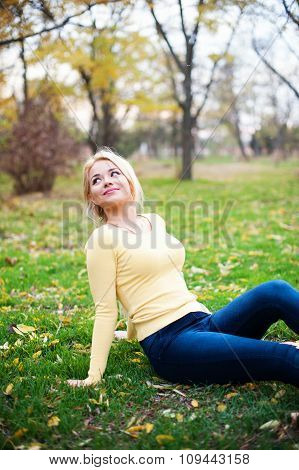 Smiling happy young girl sitting outdoors looking away