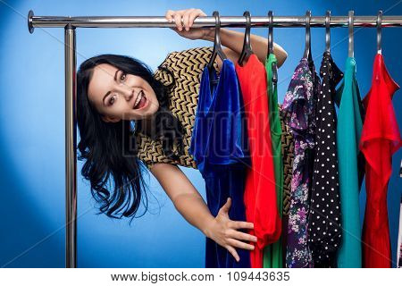 Happy Woman At The Clothing Rack With Dresses