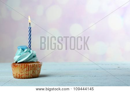 Sweet cupcake with candle on blue wooden table against blurred background