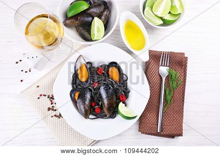 Cooked pasta, mussel, lime and wine on white wooden background
