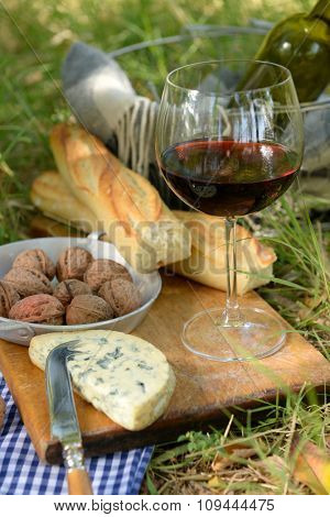 Wine, delicious cheese, walnuts and baguette on wooden board, outdoors