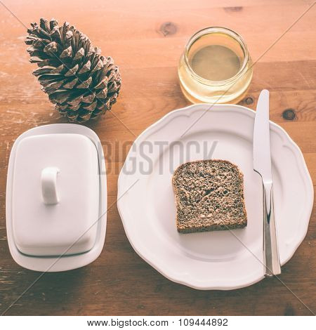 Healthy morning breakfast, bread and honey with home made butter. Pine-cone decoration on vintage wooden table