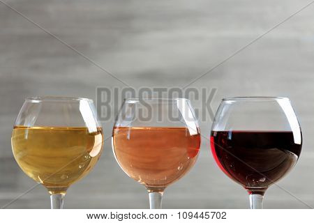 Wine glasses in a row on grey background, close up
