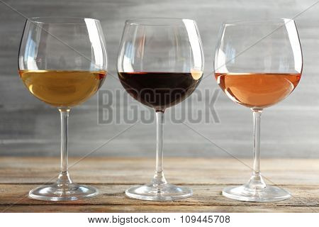Wine glasses in a row on wooden table against grey background