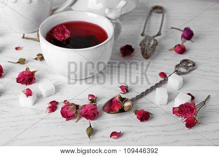Tea and tea rose flowers on table closeup