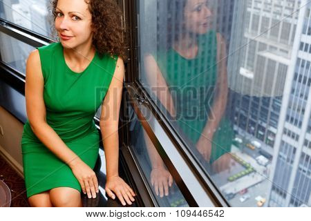 Woman sit on a sill against the background of the city through a window