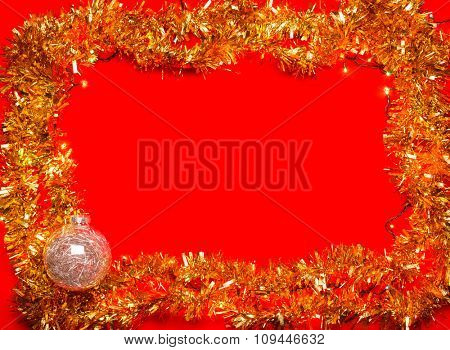 Christmas baubles with lights and tinsel frame on red background