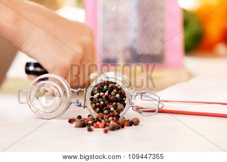 Mix pepper spices in the glass jar on kitchen table