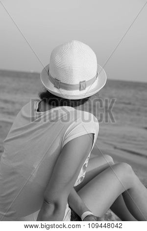 Girl Brunette In White Hat Looking At Sea While Sitting On Beach Black And White