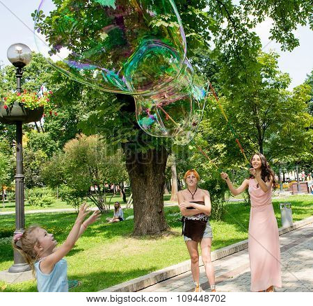 Kiev, Ukraine - August 8, 2014: Unknown Girl In Pink Dress Inflates Huge Soap Bubble In The Park