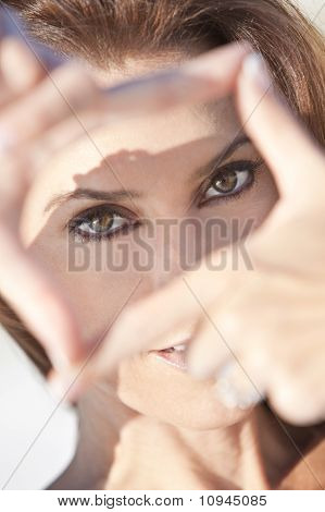 Beautiful Woman Looking Through Her Hands Making A Frame