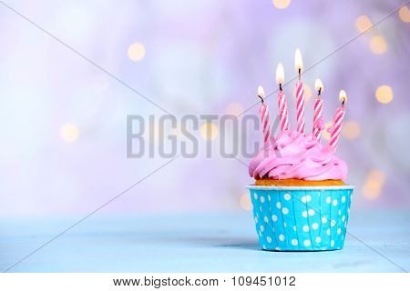 Sweet tasty cupcake with candles on blue wooden table against blurred background
