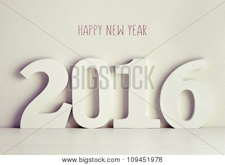three-dimensional white numbers forming the number 2016 on a white surface against a white background and the text happy new year written in red