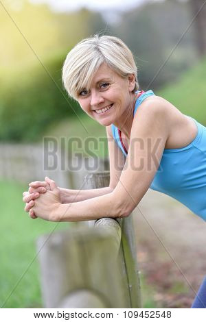 Portrait of athletic senior woman leaning on fence