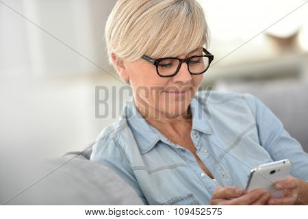Senior woman with eyeglasses sending text message