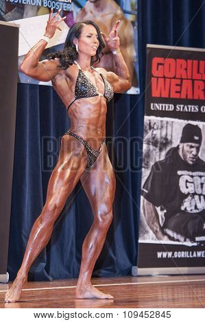 Female Bodybuilder In Double Biceps Pose And Black Bikini