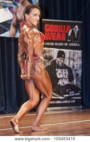 Female Bodybuilder In Triceps Pose And Red Bikini