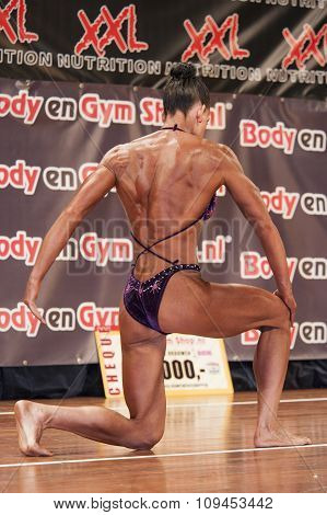 Female Bodybuilder In Purple Bikini Performing On Stage