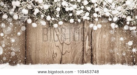 Christmas wooden background with fir branches and snow