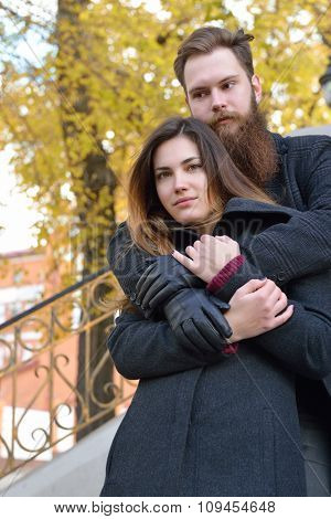 Autumn outdoor portrait of young heterosexual couple.