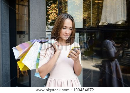 Beautiful young fashion woman with shopping bags near shop window calling smart phone