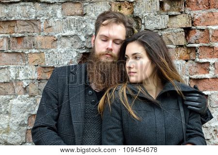 Fashion portrait of young couple, autumn outdoor against obsolete brick wall, image toned and noise added. Hipster man with beard and moustache embracing his charming girlfriend.