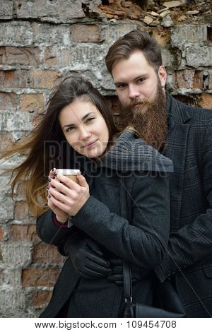 Fashion portrait of young couple drinking coffee in autumn outdoor against obsolete brick wall, image toned and noise added. Hipster man with beard and moustache