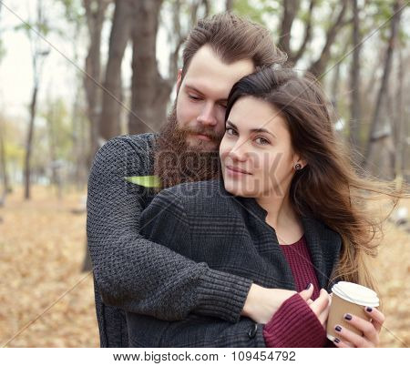 Fashion portrait of young couple drinking coffee in autumn park outdoor, image toned and noise added. Hipster man with beard and moustache embracing his beautiful girlfriend outside.