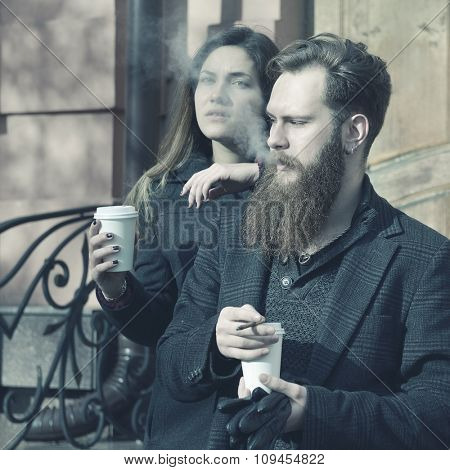 Autumn outdoor fashion portrait of young couple drinking coffee and smoking outdoor, image toned and noise added