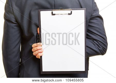 Business man holding empty clipboard with white paper behind his back