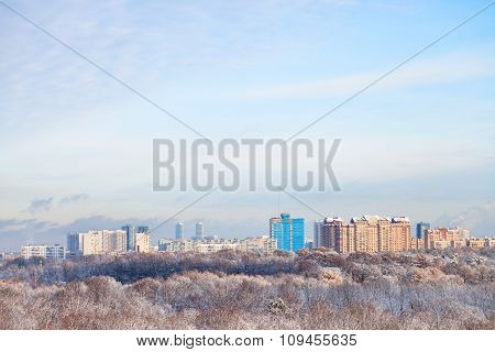 White Clouds In Blue Sky Over Snow Forest And Town