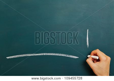 Hand drawing a white chalk line on a chalkboard with explamation mark