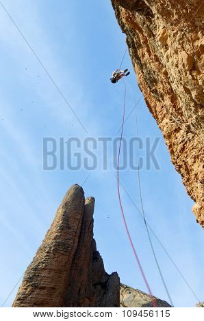 climber descending with the technique of rappelling in Riglos mountains, Huesca, Aragon, Spain