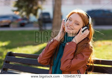 Content cheerful young woman in leather jacket and scarf sitting on bench in park and listening to music with eyes closed