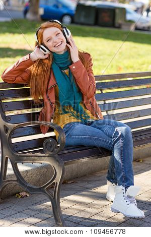 Full length portrait of young joyful pleased redhead female in leather jacket, bright scarf, jeans and white boots listening to music on the bench in the park